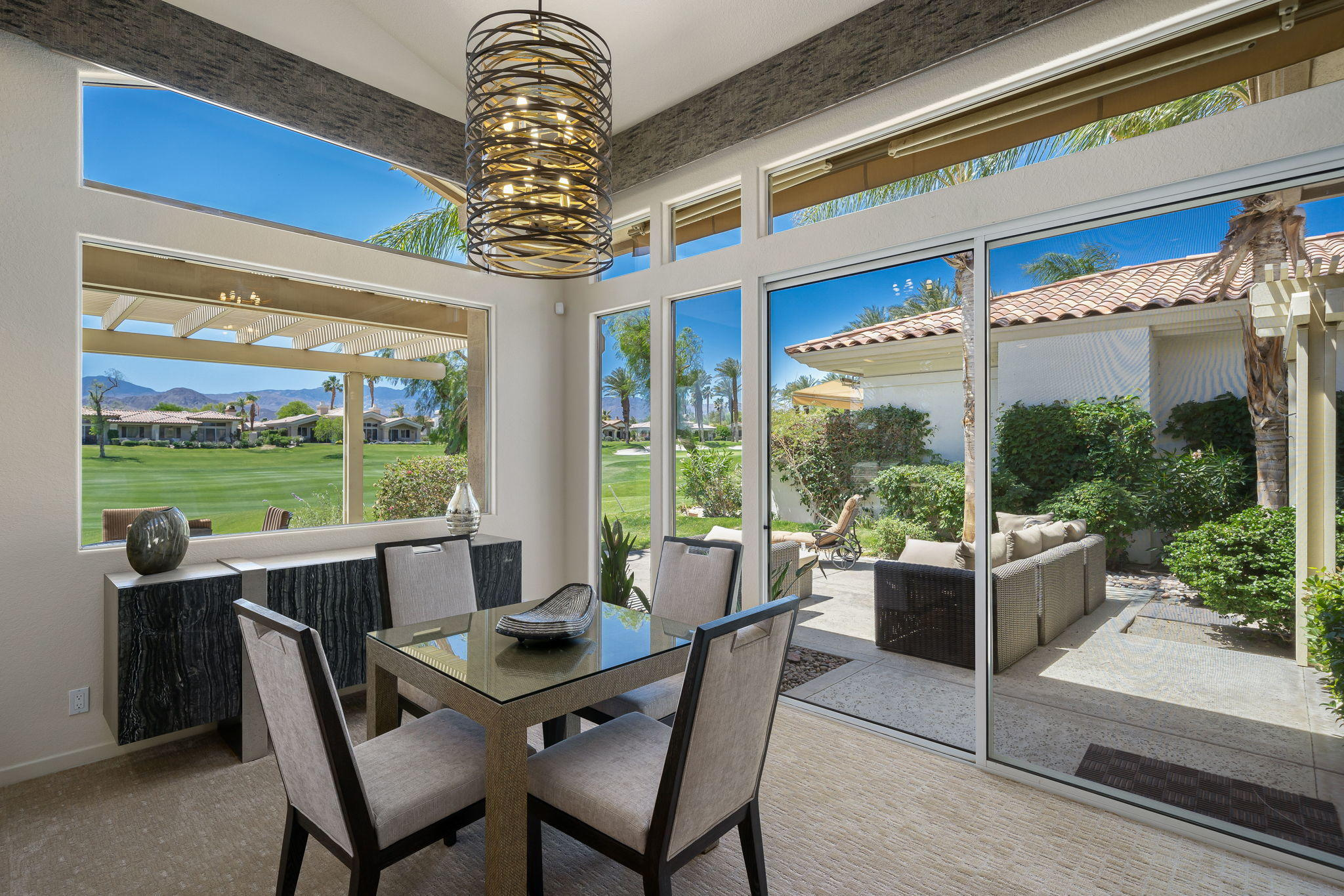 South Updated 4 Bedroom Home! This Smoketree 1 model is modified to include Casita off the atrium. Recently updated with new flooring, kitchen, elecctric shades, updated cabinetry, paint, and more! Sweeping private south mountain views over Grove #4! South-facing patio features pergola, built in BBQ and offers several areas for dining, lounging & entertaining. Open floor plan – living room, 2 dining areas, bar, & kitchen all look out to patio & those great views. Living room features a beautiful stone fireplace and is open to bar and dining area. Dining areas open out on to the patio – perfect for entertaining! Kitchen has granite counters, bar seating, updated cabinetry and top-of-the line stainless appliances. No steps at entry or foyer! Beautiful atrium off the front entry. Casita off the atrium is currently set up as an office and features Murphy bed and ensuite updated bathroom. Master Bedroom has ensuite bathroom with dual vanities, large walk-in closet, shower + tub. 2 additional guest rooms provide plenty of room and privacy for your guests – 1 guest room is ensuite. Attached 2 car + golf cart garage – epoxy floors & storage. Community pool/spa just a few doors away. Offered furnished per inventory. Club or Golf membership available for this home.