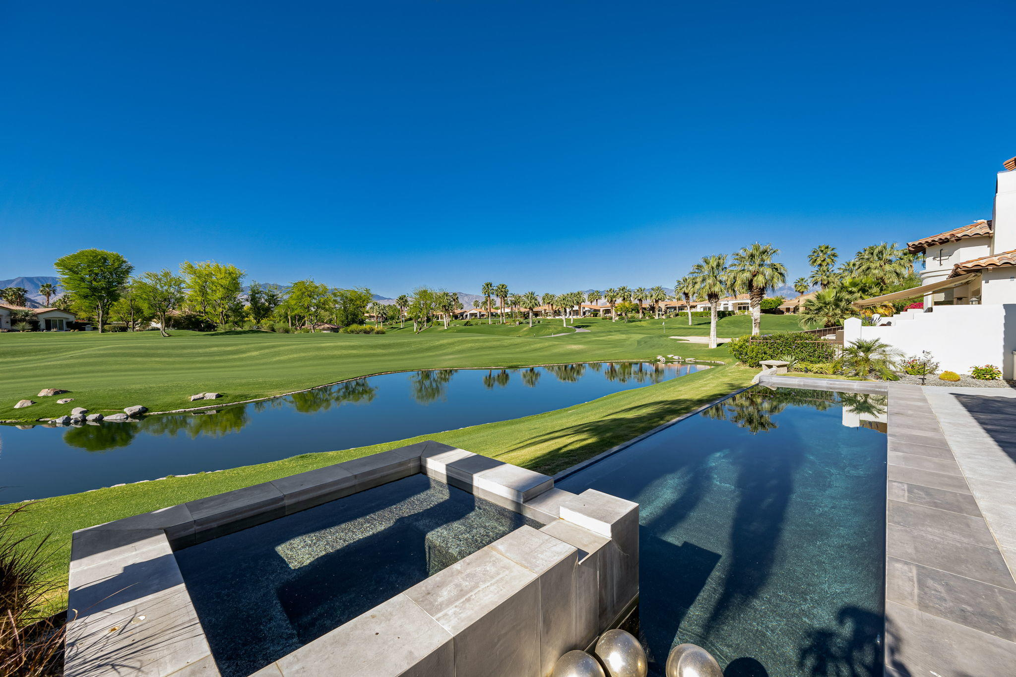 South Contemporary Pool Home! South...lake & course views! Highly upgraded interior and exterior. Located on Arroyo #15 – in center of the club, near Clubhouses. Infinity pool/spa overlooks lake – color themes LED lights in pool/spa. Expansive back patio has sweeping private south lake views. Open floor plan – living, dining, wet bar, family room all look out to the great views. New luxury vinyl plank flooring throughout + high-end carpeting in bedrooms. Kitchen features Sub Zero & Wolf stainless appliances, 78-bottle wine refrigerator & separate ice maker. Master ensuite is a luxurious retreat w/2 closets - one is spacious walk-in +built-ins. Newly remodeled master bathroom features leathered slab quartzite countertops & shower, new sinks/plumbing, Hansgrohe faucets & shower system and blue glass shower enclosure. Master bathroom also features spa tub. Two well-appointed guest rooms are en suite and offer great privacy for your guests (one is currently used as an office). Attached Casita is just off the courtyard – 1 bedroom + ensuite bathroom. Individual laundry room. Landscaping newly redesigned to include pavers, faux turf & new plants in courtyard/front yard/driveway. Attached 2 car + golf cart garage. Golf or Club membership available!