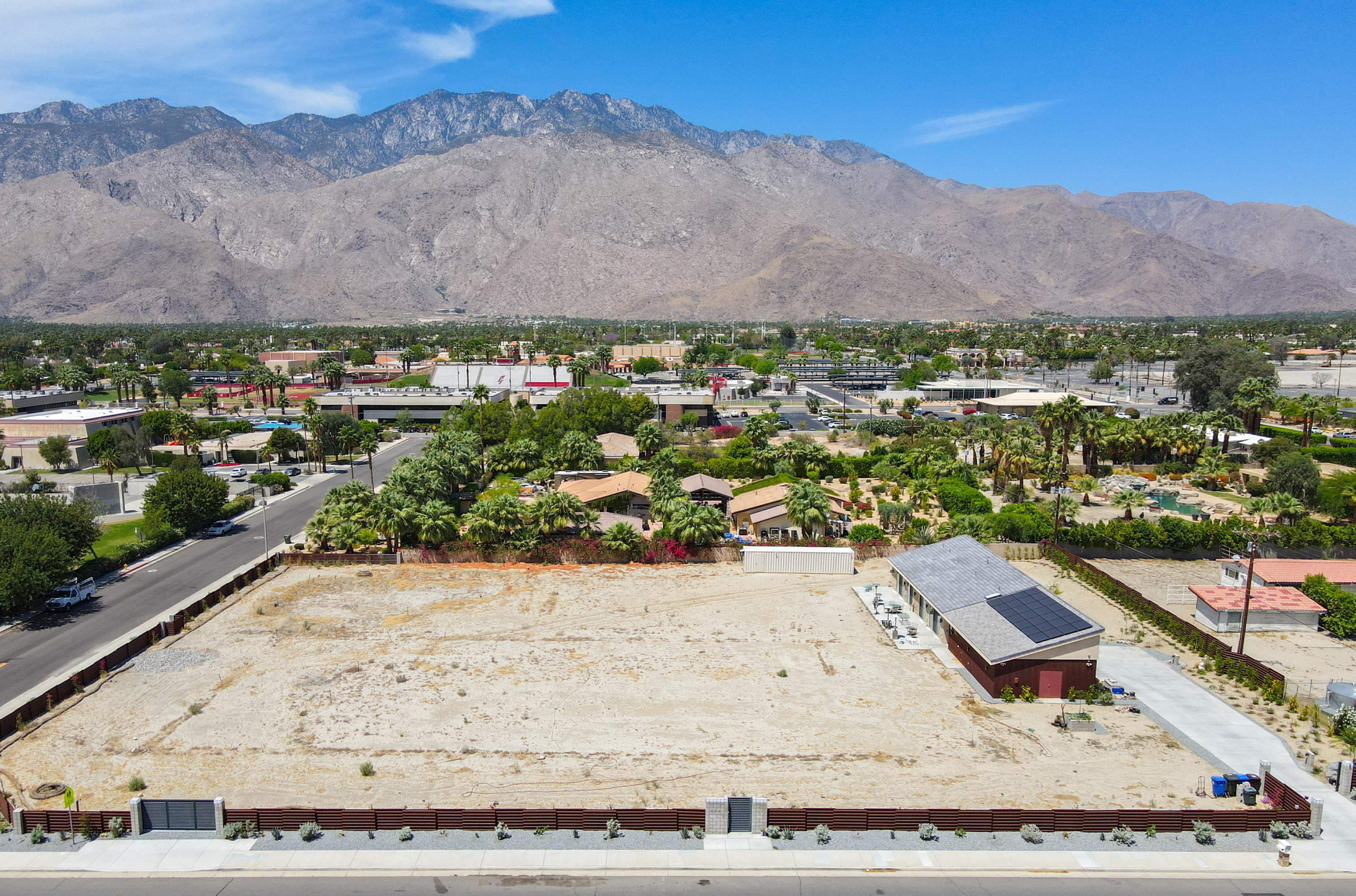 Amazing development opportunity for a private estate. Nearly 1.5 acres with unobstructed breath taking views in the heart of Palm Springs. This site is ready to go and already has a 1606 SF 2 bdrm 3 bath home Built in 2018.  Oversized 2 car garage with 2nd floor significant, carpeted/AC storage space.  Including a 250 lb load dumb-waiter lift.  All the ''heavy lifting'' has been done in order to easily build a dream main house, pool, spa, gardens and recreational areas including possible tennis court, pickle ball court and large 2nd garage and parking spaces.  Priced extremely well for all that is already here including this large lot.  Entire property is walled & fenced (CorTen steel.)  Current home has 2x6 construction and is fully insulated  (R-52 ceilings/ R-32 walls) 28-panel/Panasonic OWNED solar system  & space to add 21 more.   Separate grey water sewage system   plus Dual Potable water systems from Desert Water Agency AND the HOA-owned private well with tier 1 DWA rates for low-cost water expense for landscaping & home use. Guest house has both systems.  Two tankless water heaters. 600 Amp electric system, 30 Amp RV H2O/water/sewage dump at driveway, 240V electric car outlet & 3rd breezeway entry bathroom for future pool use and  for RV guests. There are simply no other flat, ready-to-build lots in Palm Springs available at such a value!  Forever mountain views & even zoned for horses! Not far from downtown and easy access to east valley cities too. A Real Find