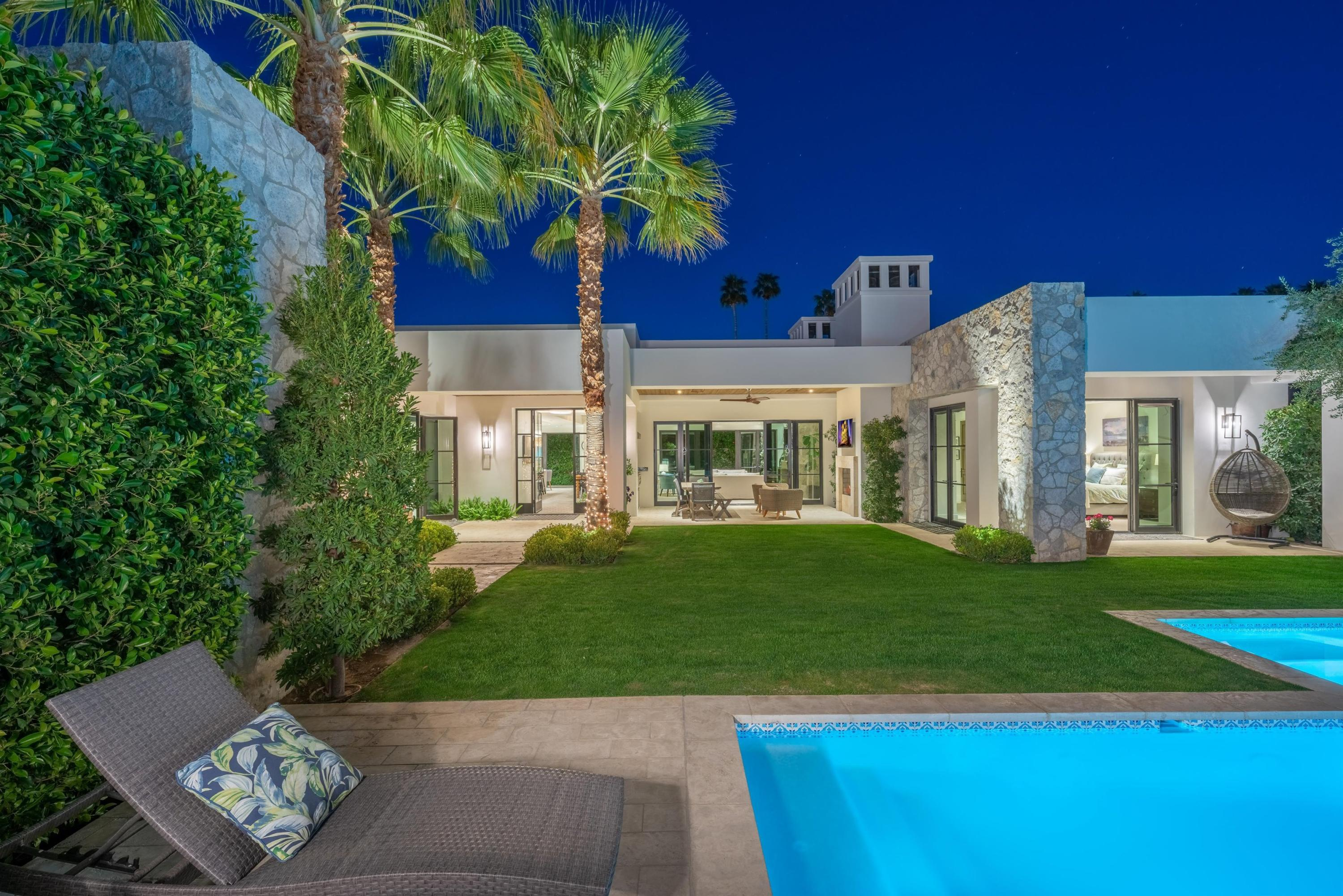 If privacy and seclusion is your desire - this desert oasis will fulfill. Tucked discreetly behind a massive iron door is an exquisite property built in 2019.  The open great room features 13+ft. ceilings with wood beams and stone accent walls and fireplace.  The multiple posh Kolbe windows and doors with high efficiency tint bring the outside in for morning breezes and natural light.  The kitchen features Rohl faucets and Shaws of England double farm sink. There is a 48' dual fuel Wolf range with two ovens, Thermador custom paneled tower refrigerator and freezer and a large white Pentalquartz island. There is a walk-in pantry with a 2nd full size refrigerator. In addition, there is a laundry/staging/storage room with roll out wrapping paper station.  Offering Visual Comfort and Restoration Hardware - the lighting throughout this Smart home is stunning.  The interior doors are vertical grain riffed cut oak. The master suite offers a fireplace and stunning mountain views along with two walk-in closets and dreamy bath. There are 3 more guest suites and a designer powder bath.  A TV/Media room also opens to the yard area.  The outdoor living/dining room feature fireplace, TV & 36' Lynx grill. The pool and spa feature Zanzibar white pool finish of mini pebble with pool tile imported from Tunisia. A full 3 car garage features new epoxy flooring. For the most discriminating taste you must see to appreciate this impeccable property.