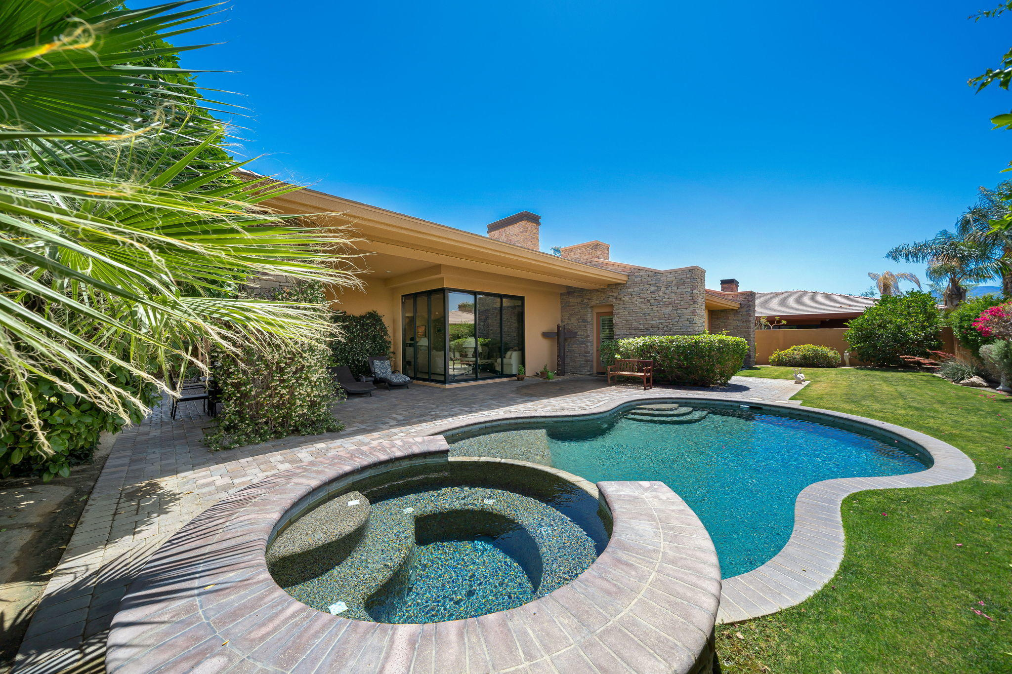 A curved driveway welcomes you to this sensational La Quinta home where style and elegance highlight the finest in contemporary comfort. One entire wall of the great room is done in stone and features a fireplace and built-in shelving. The elegant main living areas have tile floors, recessed lighting, and an earth-tone color scheme. Floor-to-ceiling windows frame your magnificent mountain views while the ultra-modern kitchen has stainless steel appliances, granite countertops, and a center island. You'll also have a wet bar for more memorable entertainment. There are three carpeted bedrooms, one of which is being used as a den, and three baths.  Double doors lead to the backyard where mature landscaping ensures your privacy as you're cooled by the misting system on the stone patio. End your evenings at your shimmering pool and spa under the desert night sky. You can relax here knowing you're protected by security 24 hours a day, and you'll be close to great shopping, dining, and entertainment options. This is a wonderful place to start living your dream desert life, so come take a tour while it's still available!