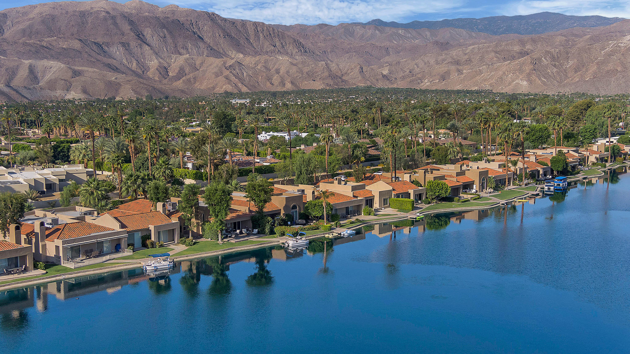 Beautiful lake front location with expansive views to the mountains. Lake Mirage offers a resort style setting offering a variety of fun Clubhouse activities,  11 Pools and Spas, 9 tennis courts, 2 Pickleball courts and 3 hole pitch 'n' putt golf course.  This 3 bedroom [one is currently used as a DEN] , End Unit, has high ceilings, private dining room with rock waterfall atrium and a kitchen with breakfast room overlooking the lake.  Hardwood flooring, crown molding and fireplace with marble detailing are just a few of the interior features.  Enjoy outdoor dining on the expanded patio.  Private Dock. Boat is included.  Central Rancho Mirage location within minutes to shopping, dining, Theater, Eisenhower Health Center, hiking and a 20 minute drive to Palm Springs International Airport.  This is the perfect weekend get-away or forever home.