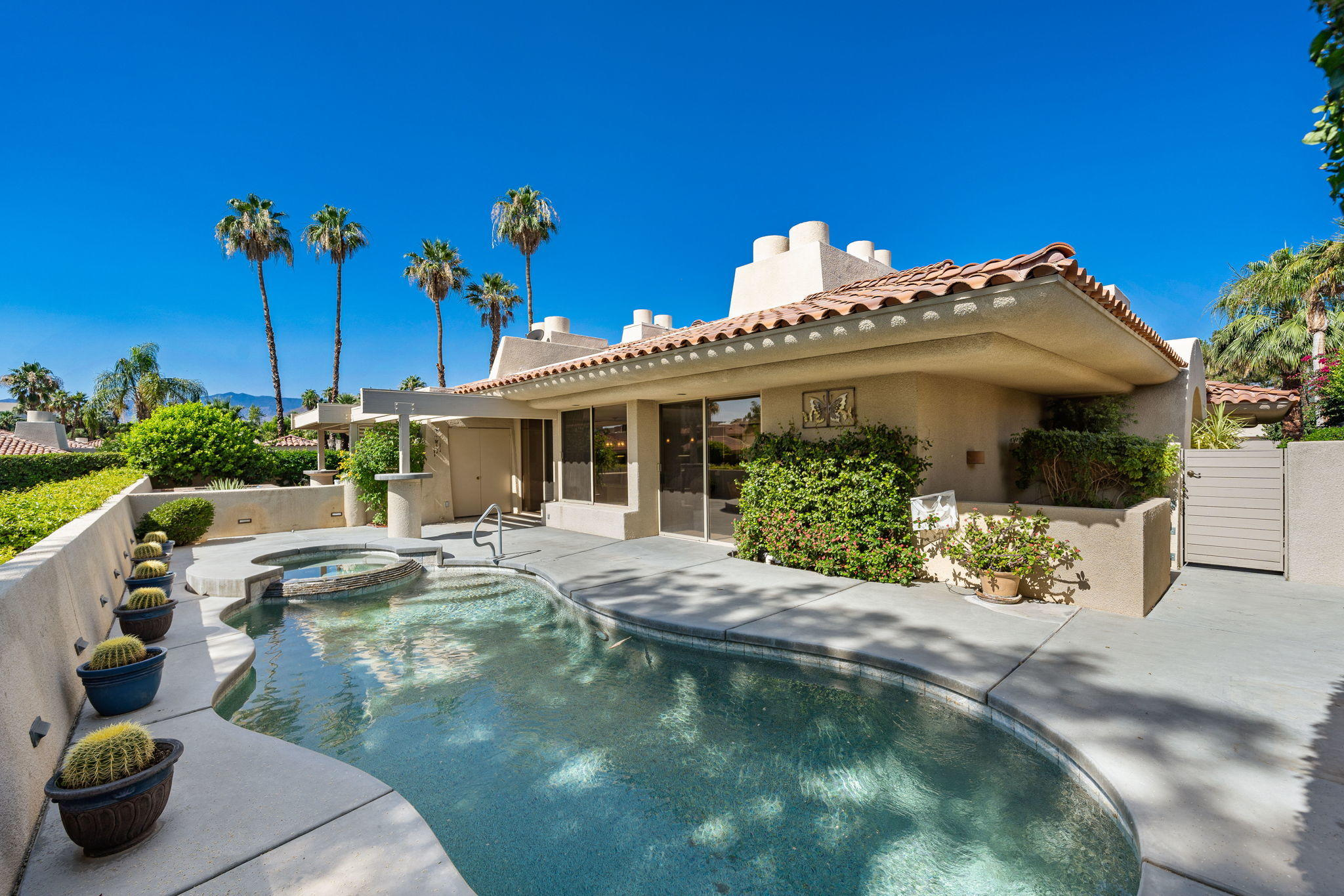 Just reduced and priced to sell in the heart of Rancho Mirage!  This spacious 3bd/4bath home, features high vaulted ceilings, Travertine floors, updated kitchen and bathrooms. At 3,246 sq ft this is one of the largest  plans at RMCC, and features an elevator! The living room offers beautiful views, fireplace, bar for entertaining, and dining area. Sparkling Pebble tech pool and spa, overlooks a peaceful greenbelt and lake setting. Gourmet kitchen with custom cabinetry, granite countertops, island and high end Dacor oven and range. There are two large primary bedrooms, and a third guest bedroom that is currently used as a den. One primary suite features a fireplace, balcony and oversized walk in closet. Located close to  Eisenhower Hospital, dining, shopping and entertainment! Palm Springs and El Paseo are mere minutes away.