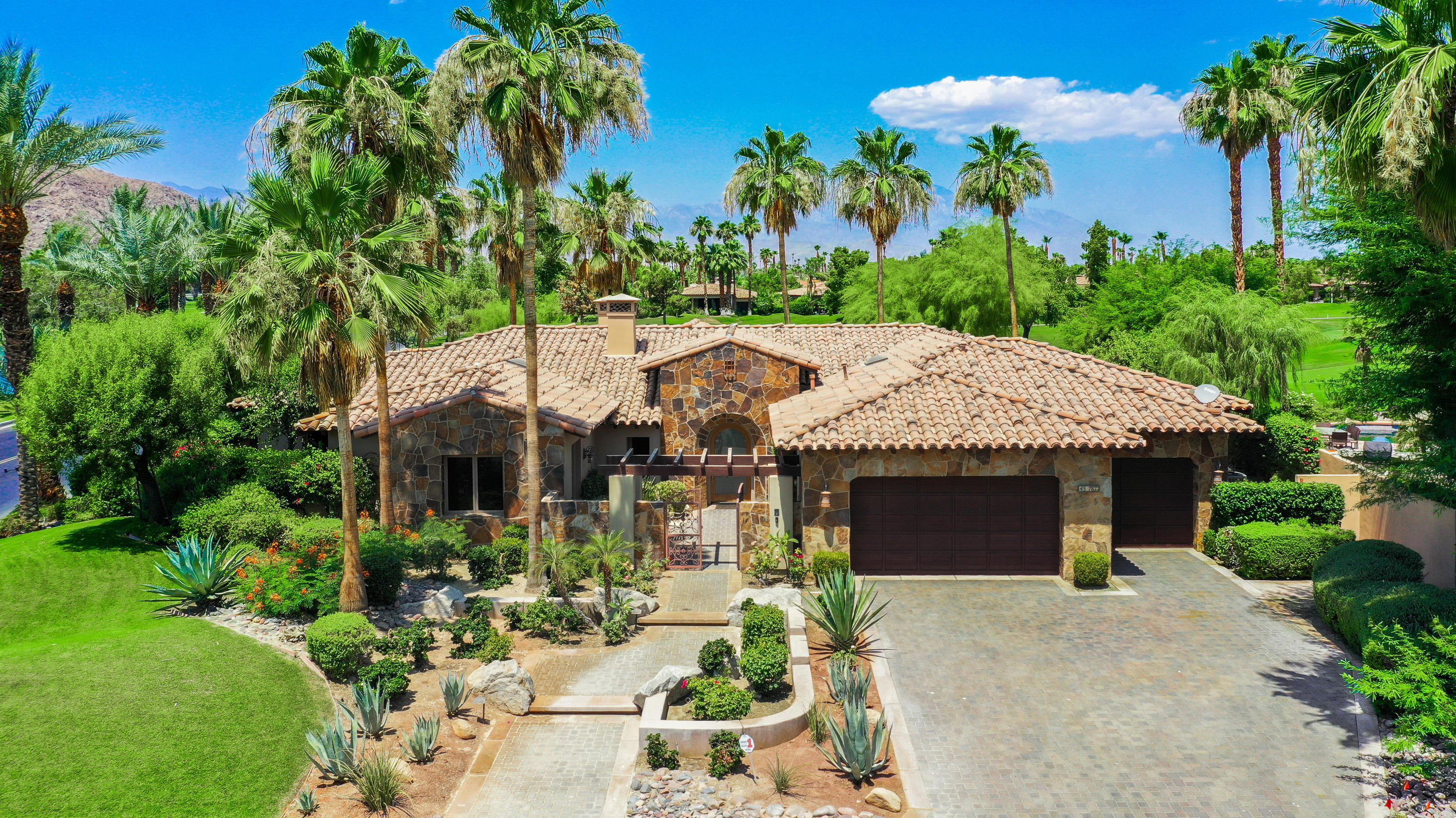Fabulous Ministrelli semi-custom home sold furnished, west facing, triple fairway and mountain Views located within prestigious Villaggio community  at Indian Wells CC.  Built in 2004, Tuscany inspired 3448 Sq. Ft. home has 3 Bedrooms with en-suite Baths and walk-in closets, 3.5 Baths, plus spacious   4th Bedroom / Office/Den, 2 fireplaces,2 car plus golf cart garage & separate entry Guest Casita on 13,939 Sq. Ft. choice Corner lot. Pavered driveway, walkway, and inviting gated Courtyard. Double door glass Front entry into Great Room with high ceilings and panoramic mountain, fairway and pool views.  Travertine pave style stone floors, custom carpets in bedrooms, custom shades and shutters. Great Room features fireplace and media center with spectacular mountain and fairway views. Exceptional Wet Bar with storage, bar refrigerator, and bar seating.  Open Gourmet Kitchen with views has wine room, large pantry, granite countertops, stainless appliances and big Kitchen Island.  Private Master Suite boasts views, private patio and 2 walk-in custom closets. Spacious Master Bath has jet tub, travertine countertops and glass shower, dual sinks plus vanity. Outdoors has gorgeous views and sunsets, pebble tech pool and spa, covered patio with built-in fireplace, and BBQ island which all embrace this desert paradise!