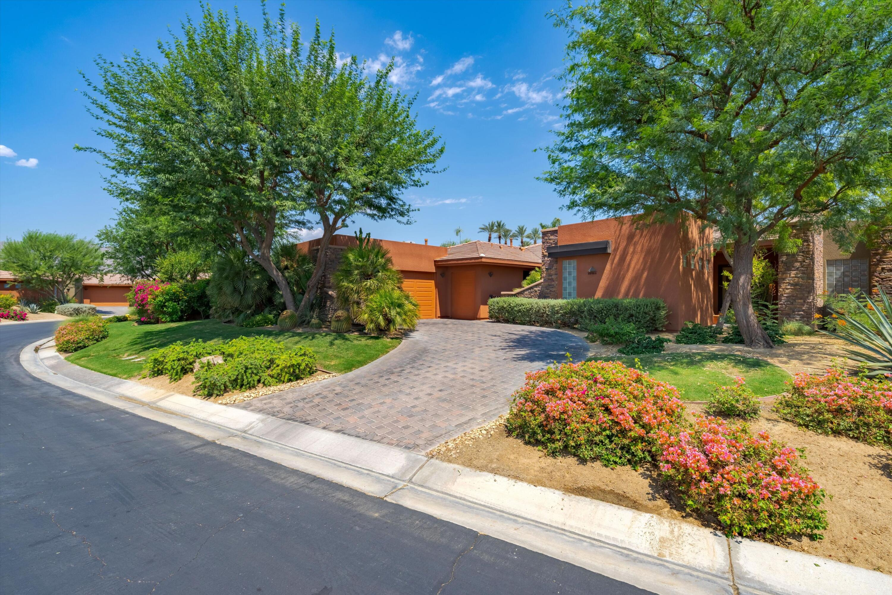 This contemporary, desert-inspired floor plan with its two master suites plus office was awarded the Best in America Living Gold Award in 2002.  Strikingly modern w/angular lines this great room home sits on a knoll with a along driveway for extra off street parking. The interior location, tucked away in a quiet cul-de-sac, allows you to cocoon away from the world. A focal point stackstone fireplace & an expertly crafted interior boasts tall ceilings, floor to ceiling Low-E glass, French doors, surround sound (great room & patio), and cherry cabinetry providing a warmth to the contemporary lines of the home. An expansive patio with interlocking pavers surrounds the beautiful angular 42 ft. pool & spa with waterfall, elevated planters, a buillt-in BBQ island, with beautful low-maintenance desert landscaping.  The gourmet kitchen features slab granite counters, an island w/sink, pantry, stainless steel appliances, a gas range with chimney-style wall vent, double ovens & a  microwave. Amenities include a sunken wet bar, upgraded flooring, dual walk-in closets in the main master bedroom, travertine baths, dual zone central air conditioning. The 2 car garage plus golf cart area has a workbench and cold room for storage. With a 24 hour gate guard the HOA covers so much in this award wining development (itemized in attachment) with its beautiful waterways & lakes. Located w/easy access to the amenities of desert living- shopping, golf, tennis & restaurants. Truly a beautiful home.