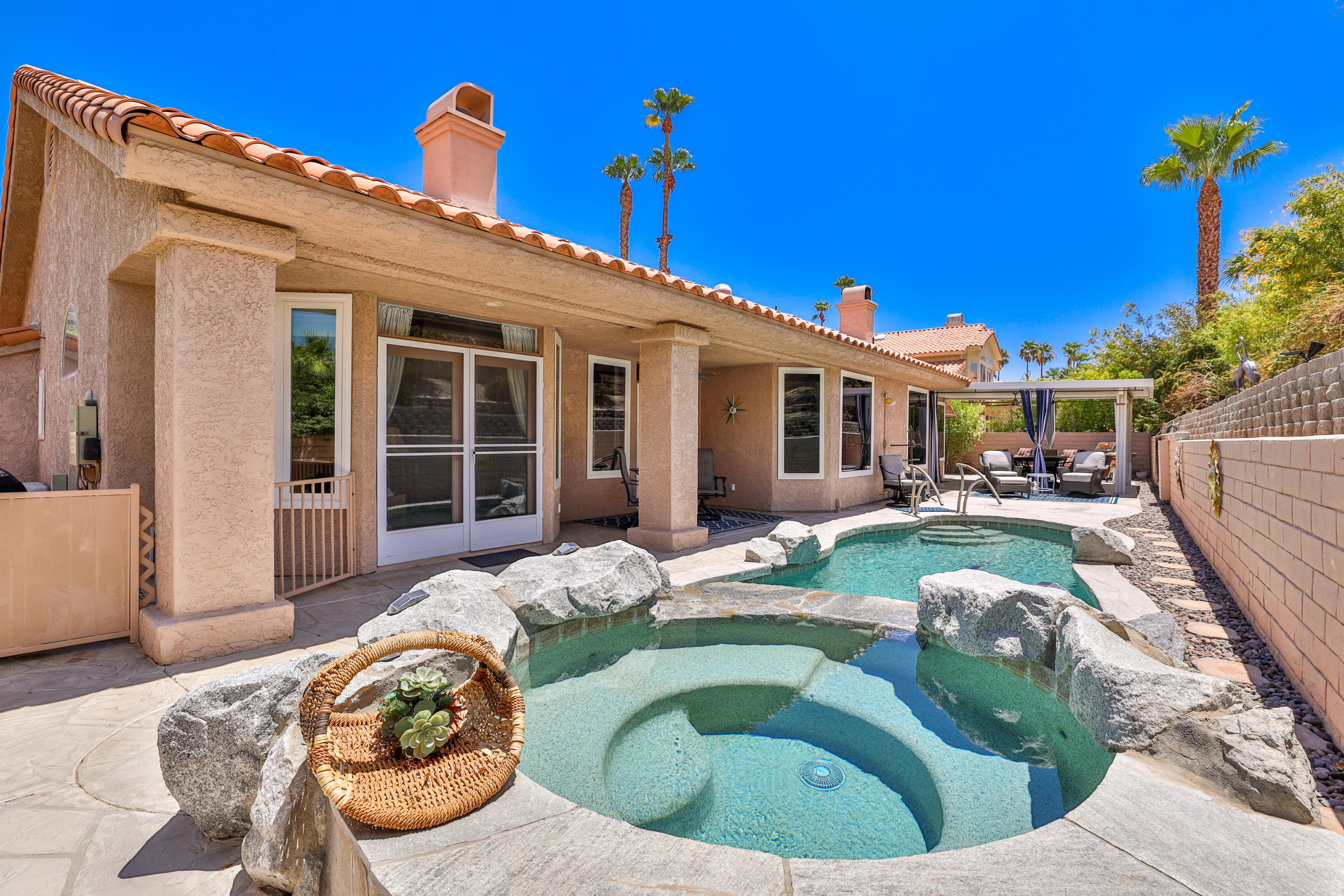 Introducing this beautifully updated home in The Links neighborhood in Desert Falls Country Club. Boasting over 2,500 sqft., the home is equipped with 4 bedrooms(one being used as a den), a large living and dining area-plus a large family room that is open to the kitchen. The large primary suite, with its own fireplace freestanding tub, custom cabinet and picturesque views of the pool/backyard, will be the perfect way to enjoy the comfort of your desert oasis. The kitchen is complete with beautiful granite counters with counter top seating, stainless steel appliances, and ample amount of cabinets for all your kitchen needs. Windows galore, multiple French doors and solar tube creates maximum natural sunlight to permeate throughout the kitchen, family room, dining room, living room, and master bedroom. The tranquil backyard is outfitted with pergola-style gazebo awning with privacy drapes, stamped concrete, pebble tec pool/spa with exquisite rock features and mature landscaping. Homeownership includes HOA maintained front yard, fitness, tennis, pickle ball, bocce ball, horse shoes, and ladder toss. The fitness facility includes circuit machines, free weights, aerobic machines, and classes. Desert Falls, conveniently located mid-valley with easy I-10 access, close proximity to groceries, dining, and retail. This truly is a one-of-a kind property!