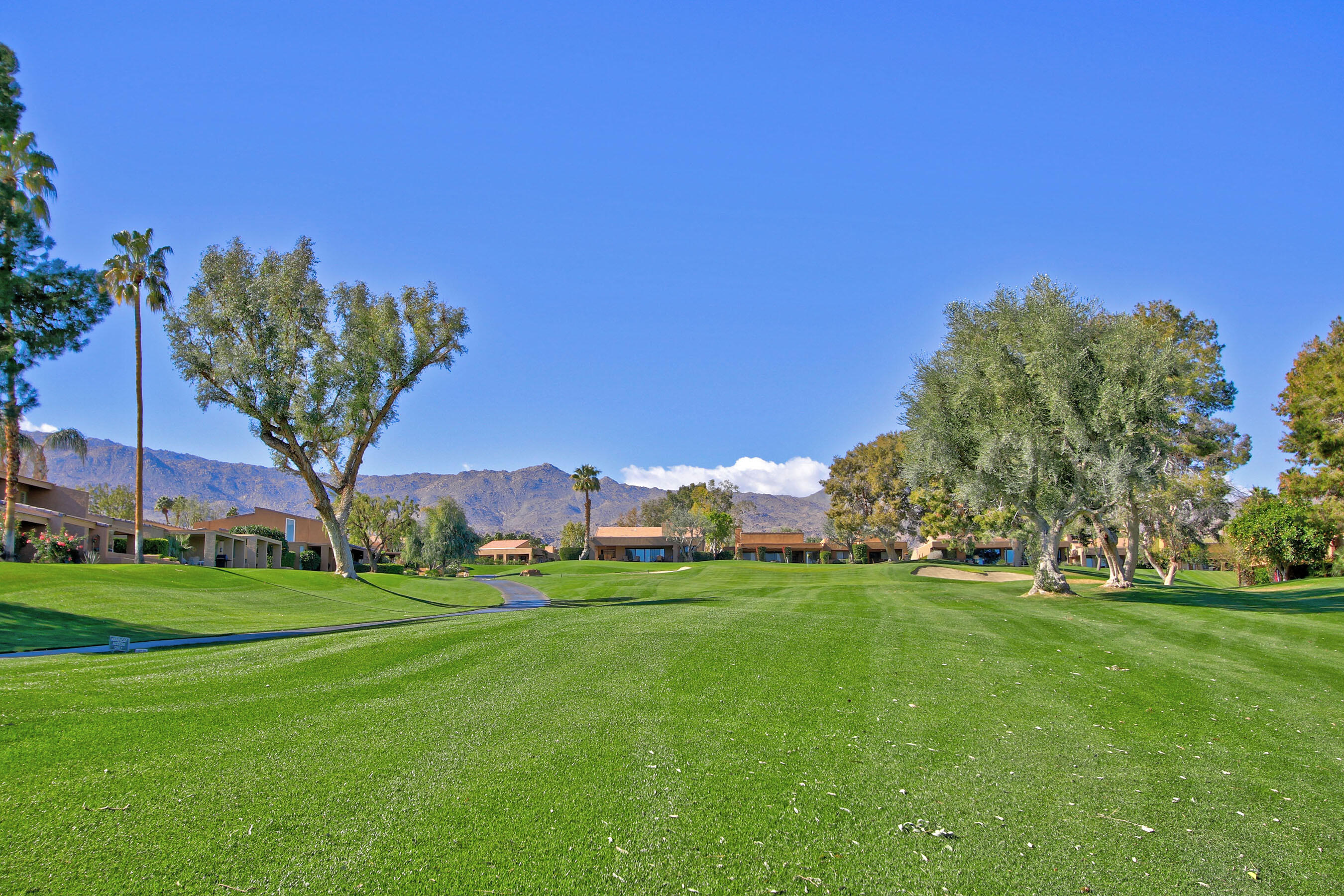 Golf Course location with Southern mountain views! Enjoy the perfect desert lifestyle in this Fairway Resort plan with high ceilings, lots of light and open Great Room design. Tile floors in living areas and bamboo flooring in the bedrooms. Open kitchen with granite counters, double ovens & pantry in the adjacent laundry room. Master suite has large bath, tile shower and walk-in closet plus added office area overlooking the 11th/12th fairways. Office has granite built-in double desk and room for a sitting area. Guest suite has private bath and patio area. There is a powder room in the hall. Patio area is tiled and expanded with privacy wall and also has firepit and southern mountain views. Impressive entry at the end of the cul-de-sac with interlocking pavers and a long driveway for extra parking. Entry courtyard patio has custom glass gate and double glass entry doors.  Double garage access into laundry/pantry area off kitchen. This has been full-time home and is immaculately maintained.
