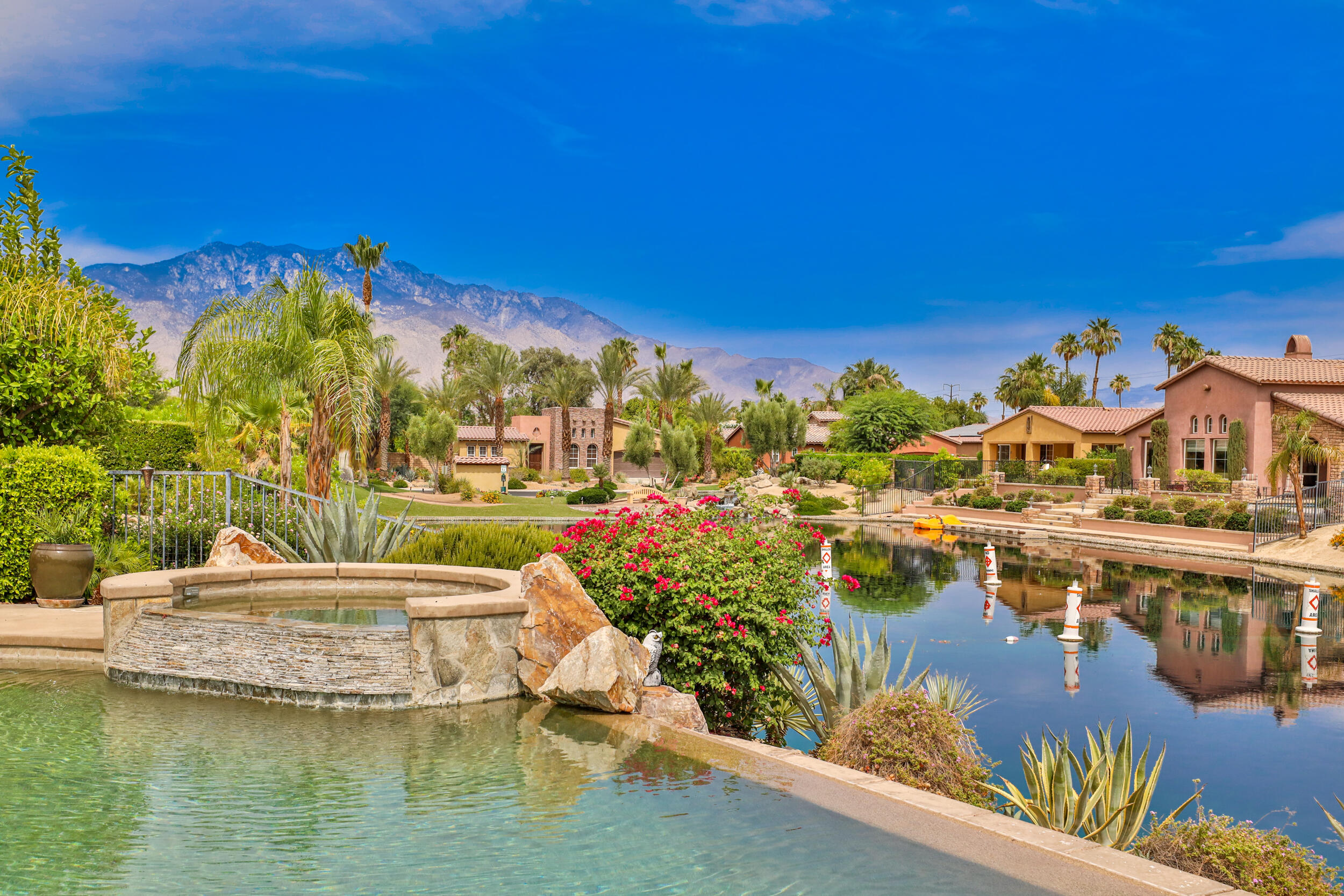 Gently lived in vacation home of original owners.  Over 13,000 sq foot waterfront property located on quiet interior cul de sac of last waterfront development approved by Rancho Mirage.  With the Versailles travertine flooring, 9' ceilings and 8' crown moldings throughout, you will feel transported to the Tuscan countryside.  Enjoy views of the Santa Rosa Mountains from the backyard while lounging by the 42 foot infinity pool.  An entertainer's delight, the formal dining room flows directly into an intimate interior courtyard for you and your guests to relax with an after dinner drink while enjoying the star filled sky.  The large open concept kitchen and family room provide the perfect space for informal gatherings.  The master suite with French doors into the courtyard, is located away from the guest rooms ensuring you and your guests' privacy.     Santo Tomas is a beautiful, quiet and unique development for the sophisticated buyer.  The HOA is very well run with healthy reserves and the low HOA dues includes a sport and social membership at the beautiful Mission Hills Country Club.  Listed at over $50K less than the last similarly situated waterfront home sold in Santo Tomas.  Spoil yourself and enjoy the sophisticated lifestyle at Santo Tomas – don't wait as this one won't last long!