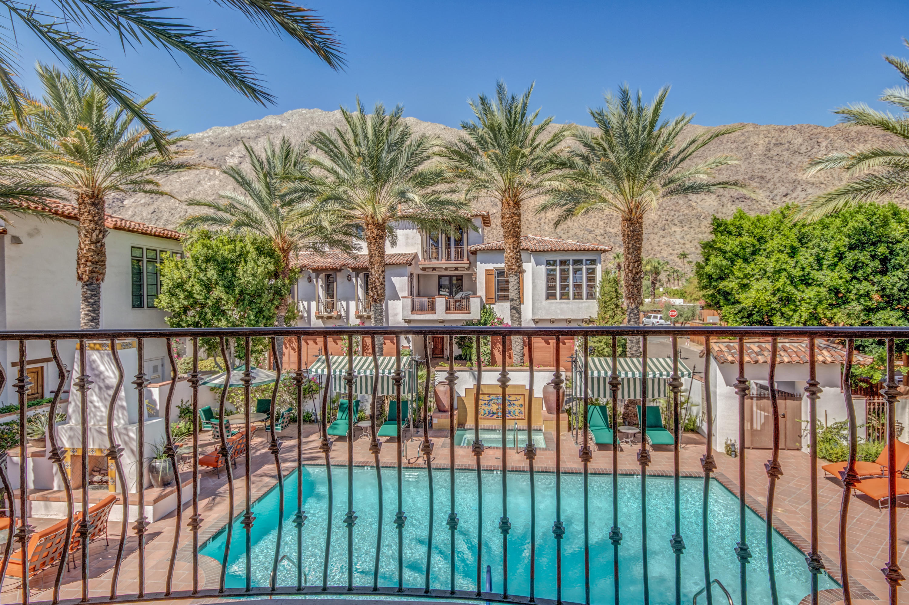 The desert's leisurely lifestyle meets Historic Tennis Club. Beautifully appointed 2 bedroom plus den and media room. Built-ins, wall-to-ceiling stonework, and overall design choices including vaulted ceilings begin to tell the story. BBQ space with its custom wrought iron design is a jaw-dropper. The ''Batchelder tile'' inspired fountain is exceptional. Living room is framed by a series of 10-foot French doors opening to wrap around patios. Kitchen upgrades include custom granite countertops, high end appliances, and designer cabinetry. This home's designer took great liberty in creating a space that is ANYTHING but cookie cutter. Breakfast area opens to patio in grand fashion. Formal dining is yet another option. Home office is currently used as a guest room. Upstairs TV room / den includes wet bar with stone backsplash. Master suite enjoys a patio looking out over the town. Double sinks, stunning finishes, and oversized master closet is located within the master bath. Laundry is located upstairs. St Baristo's pool area is world class. Think Italian Riviera meets Slim Aarons' photo shoot! Proximity to walkable historic neighborhoods hugging the San Jacinto Mountains in Old Palm Springs is another plus. Restaurants and shopping are a couple blocks away. So much to love. You'll find it here!