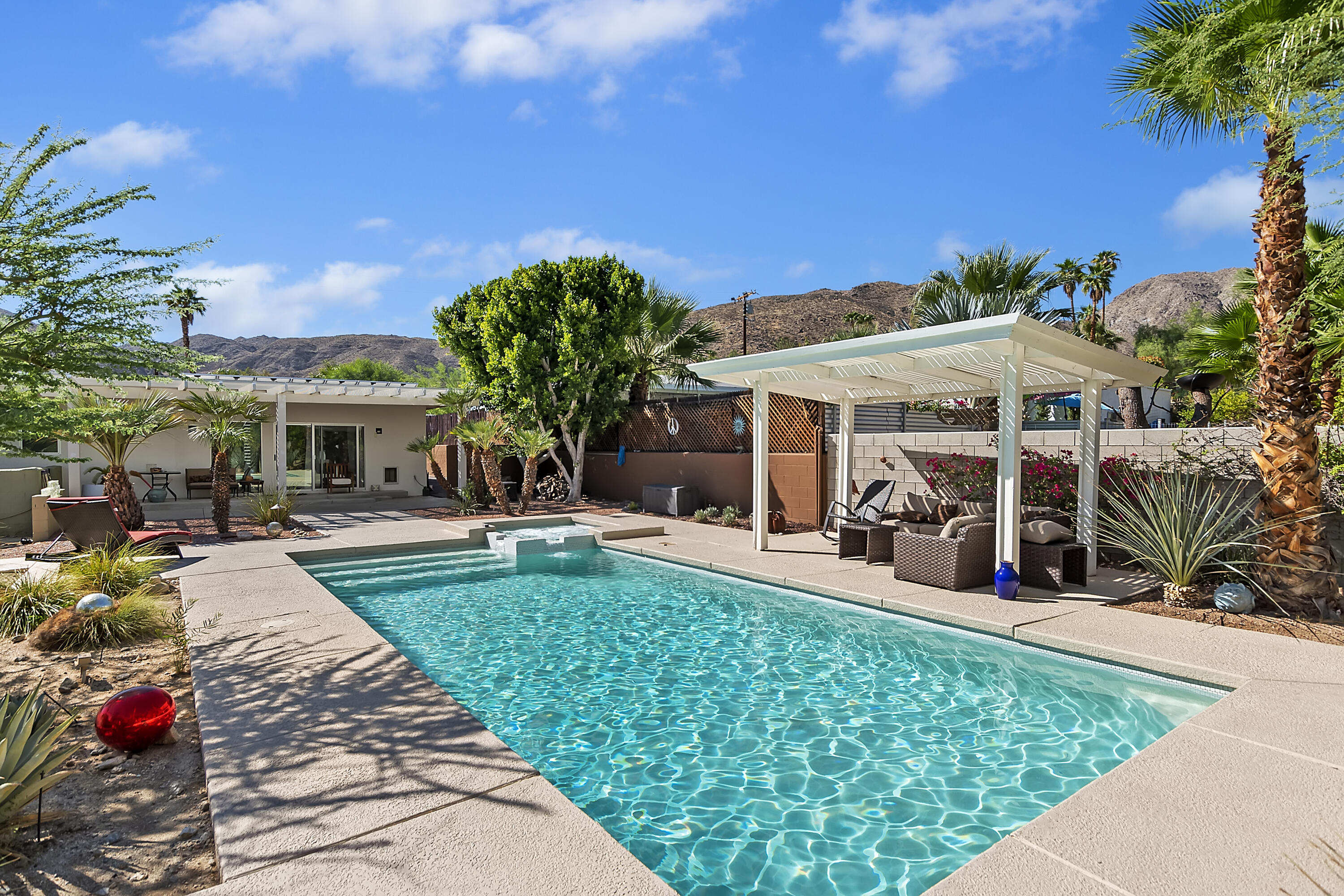 Are you looking for a larger than average mid-century home on an almost half acre that affords total privacy, a view, a European flair, a view, 2170sq ft (per assessor), and did I say a View?  Then, you have found it! Built in 1969, This beautiful updated 2+, high atop the Cathedral Canyon Cove features concrete floors, wood paneling and beamed ceilings with halogen spotlights throughout. The upgraded galley kitchen includes stainless steel countertops, a Sub-zero refrigerator, a 6-burner gas stove top and Kitchenaid oven, a huge pantry, and lots of cupboard and cabinet space. The kitchen sliding glass doors opens up to a large patio that exposes a beautiful northern view of the valley. The living room is large and bright with windows that also open up to both mountain and valley views. Both oversized bedrooms have sliding glass doors that open up to the resort like, most private, back yard. Both bathrooms are upgraded, European in nature and design, and are also spacious. The primary bedroom has a ceiling fan, and a large walk in closet.  The back yard is both beautiful, very calming and peaceful. A large salt water pool and spa is the focal point that is shared with a pergola, fire pit, and cool decking. North of the pool area is a lush garden area with native palo verde trees, a cactus garden and a small walking trail. There is RV parking.. *The AC system is 2020 new. The home comes with OWNED (not leased) solar. The roof has recently been upgraded to foam.