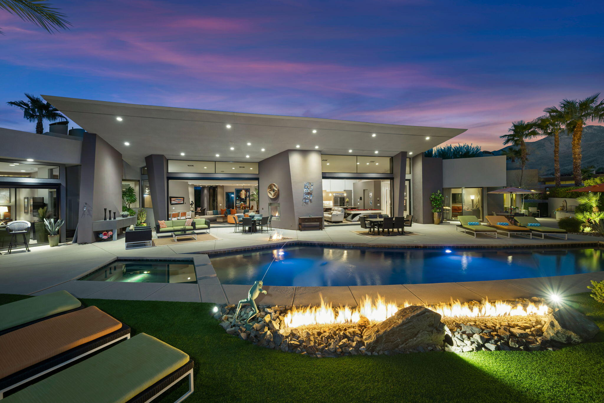 This artistically conceived top-tier estate was designed by award winning local architect Narendra Patel, and is located in the south Palm Springs gated enclave of Alta.  The home is surrounded by spectacular mountain views from almost everywhere inside and out! The two sets of motorirzed disappearing walls of glass open to one of the most breathtaking resort backyards in the desert! With the San Jacinto mountains as the backdrop, the park-like grounds include a pool, spa, outdoor kitchen, multiple firepits, fireplace, a grand rock water feature and lush landscaping!  This desirable plan includes a formal living room with wet-bar, formal dining room, a family/media room and a separate home office! The Epicurean kitchen has stainless steel appliances, walk-in pantry and substantial island with bar seating! The primary suite has a separate media/sitting area, larger steam shower, dual walk-in closets and direct access to the backyard! The additional three suites are perfectly situated at the opposite of the home for privacy! This estate comes with a fully paid and owned 14kw solar system and a three car garage! You own the land!