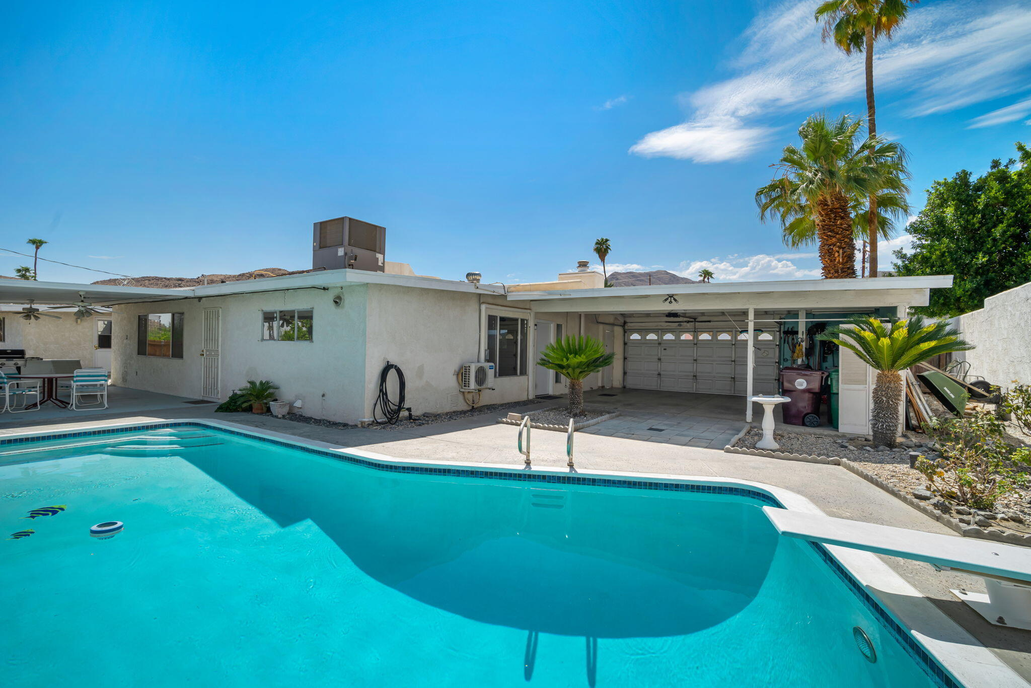 If classic Desert Pool Homes are your passion, you'll love this mid-century single story residence located in the peaceful and serene Cathedral City Cove neighborhood. Tucked away on the south side of Cathedral City, this meticulously kept home has 1726sqft. of interior living space, including 2 BD/3 BA, a separate entry living room with picture window, and a family room (with rock-encased fireplace and vaulted ceilings), which could serve as the 3rd bedroom, den/office, or left up to your imagination. Numerous upgrades to include a newer Torch Down Roof (2018), new Roof Top 5 ton A/C unit (2021), On Demand Water Heater, newer mini-split A/C Mr. Cool unit in the family room (2018) and a new water main Pet piping from the street to the house (2021). The centrally located kitchen features a dining area, built-in cabinetry/hutch, breakfast bar, newer SS LG stainless appliances (2019), tile counters/backsplash, double-sided sink and built-in microwave. Guest bedroom has adjacent full bath with shower over tub, and the master retreat boasts multiple closets, shower stall and backyard access. Vintage rear yard pool with mountain views, a new Pentair Pool Pump (2021), recently bead-blasted tiles and the surface was acid washed; there's even an ''old school'' diving board for all friends and family to enjoy. The covered patio affords shade and don't forget the open-ended 2 car garage. Close to all shopping, restaurants, Aqua Caliente and Palm Springs nightlife. Come see today!