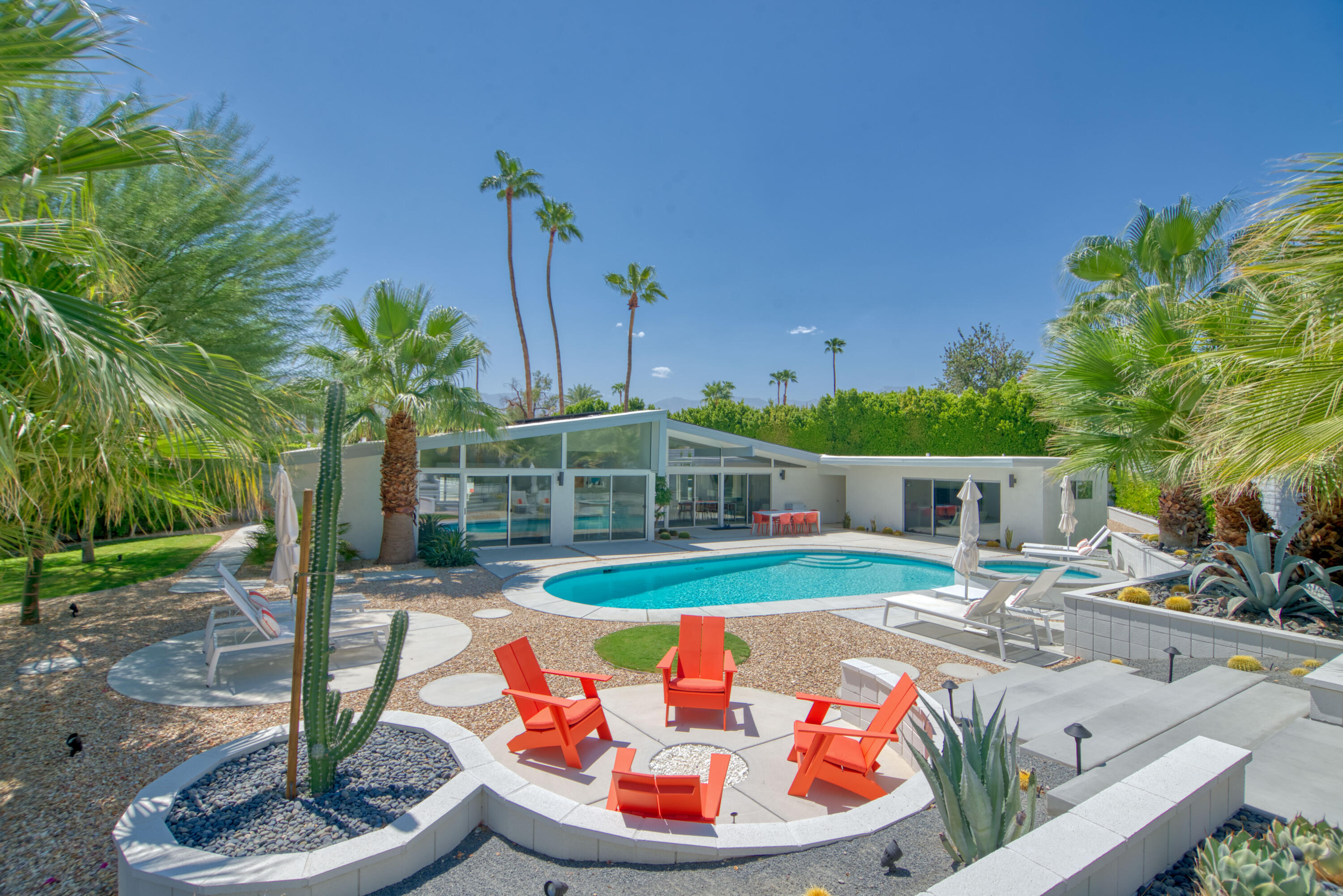 Attention MID-CENTURY MODERN enthusiasts!  Check out this renovated and beautifully-appointed 4 bed, 3 bath architectural gem located on a premier lot within blocks of Tamarisk Country Club.  Originally designed by architects Palmer & Krisel, this very special property is being sold and delivered turnkey furnished - including paid for solar panels and a Tesla Powerwall.  As an added bonus, this home has received The Mills Act designation rewarding you with a lower tax base!  You will love how the stylish kitchen with adjacent dining area opens to the light and bright great room that features a vaulted wood beam ceiling with clerestory windows, mountain views to the south and dual sliding glass doors that open to the ultra-private resort-style backyard that includes a refreshing pool, in-ground spa, gas firepit, and elevated deck.  Mature palms and mountain views frame the backdrop of this tropy property!  Master Suite features a high ceiling with clerestory windows, a sliding glass door that opens to the private backyard and an ultra-modern bath with dual sinks and a large walk-in shower with two showerheads.  Bedrooms Two and Three also offer high ceilings, views, a sliding glass door that opens to the outside and easy access to the hallway bathroom complete with a walk-in shower.  Outside is a large guest house (Bedroom Four) which includes a wet bar and another spa-like full bath.  Absolutely incredible!