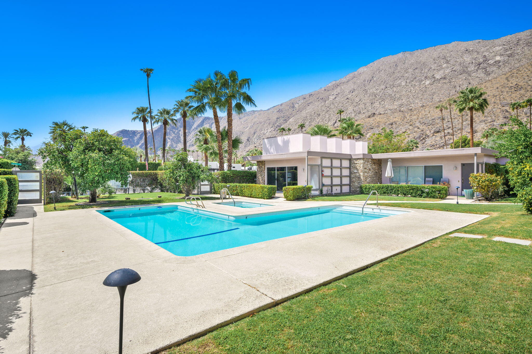 Bursting with relaxed Palm Springs style and set in an ideal location, there's plenty to love about this impressive residence. Natural light flows freely into the living room through the sliding glass doors. Designed with an open floor plan and dramatic architecture, this modern home offers a large bedroom with room for seating and a lovely bath with a walk-in shower. You'll enjoy a built-in bar, recessed lighting in the living room with direct access to the front patio overlooking the pool. The eat-in kitchen is bright and modern with stainless steel appliances and see-through cabinetry overhead.  Conveniently located on the ground floor and with no upstairs neighbors, you'll enjoy a quiet, peaceful lifestyle just steps from the community pool and spa. Beautifully manicured grounds encompass the building with plenty of off-street parking and desert mountain views for your pleasure. Set in an unbeatable location close to Palm Springs golf, shopping, dining, and nightlife, everything you could ever ask for awaits in this move-in ready home. Come take a tour before it's gone for good!