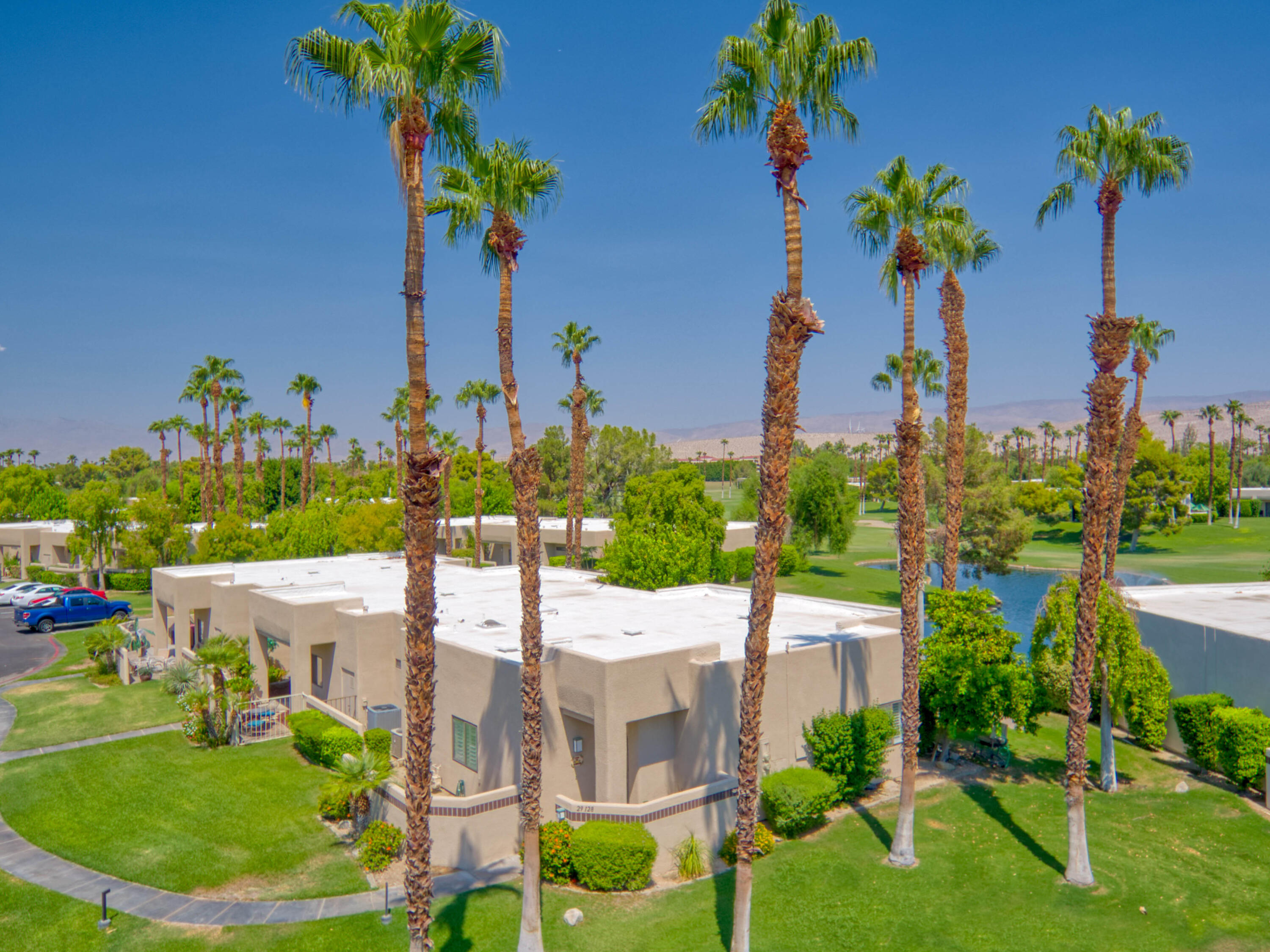 ENJOY IT ALL! Fantastic opportunity in terms of smart design, privacy, and WHAT A VIEW! Beloved Desert Princess Country Club is the magnificent backdrop. This corner condo brings light pouring in from three sides. Covered patio runs the length of the home on the lake side. Views of the Chocolate Mountains and neighboring Little San Bernardino Mountains! You'll LOVE the fountain and green space doubling as your backyard. Glass sliders bring the outdoors into the primary living areas and master bedroom. Kitchen opens in a way which makes for easy-breezy entertaining! Guest bedroom is currently enjoyed as a home office. Tile flooring and plantation shutters are timeless. Fireplace is a pleasant surprise in terms of scale and positioning. This home's magnificent double-door entry is fabulous. Laundry closet located in the hallway. This modern community is home to 537 condos and 675 freestanding villas. Be sure and check out Desert Princess Country Club's 27-hole championship golf course and 35 swimming pools. Bocce ball, pickleball, or tennis anyone? All of it, just minutes from the heart of downtown Palm Springs.