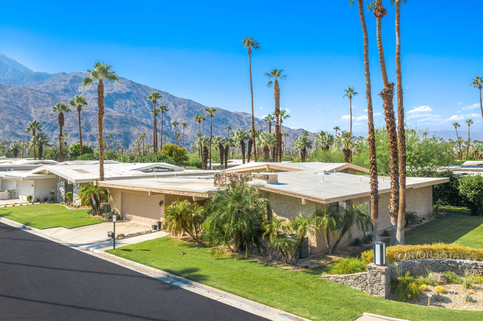 Looking for idyllic living in an active Palm Springs community? Be sure to see this highly desirable, move-in-ready residence in Canyon Estates. Canyon Estates was developed using the design of architect Charles E. Du Bois, AIA by Palm Springs developer Roy Fey. A tiled foyer invites you into a spectacular open-plan living and dining room where a wall of glass across the rear pairs with a soaring cathedral ceiling featuring wood beams and high windows that bathe the space in sunlight. Your dine-in kitchen is a chef's delight with stainless steel appliances, plantation shutters, and direct access to the tiled and covered private patio. Step outside to enjoy relaxing views of lush landscaping and well-maintained grounds. It's an ideal spot for sipping your morning coffee and enjoying al fresco meals. Take advantage of a separate laundry room and an attached 2-car garage. You'll have access to the executive par-3 golf course, 15 community swimming pools, 12 spas, two championship tennis courts, and pickleball courts. Your clubhouse features a library, a pool table, and a fitness center, plus shopping and dining are nearby on East Palm Canyon Drive. Come make this carefree lifestyle your very own before the opportunity passes you by!