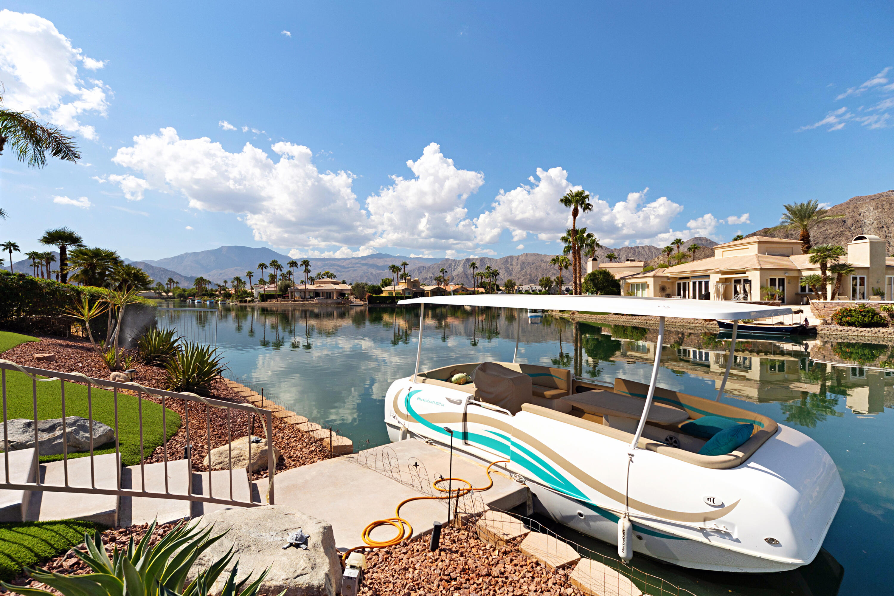 Have you ever dreamed of owning a lake house?  Great opportunity available now to own premier lake front home with amazing mountain views in prestigeous ''Lake La Quinta''.  This 2900+SF residence offer three bedrooms, three and half baths on a 12,197 SF lot.  As you walk through dramatic court yard to double doors, you are instantly captivated by the high ceilings and the large windows that provides ample natural light and unobstructed views of the shimmering lake & beautiful Santa Rosa mountains.   Master bedroom is spacious and has access to swimming pool & spa and sparkeling lake.  Master bath offer double vanity, soaking tub and walk-in shower.  Two large guest bedrooms each with own bathrooms and one has own private patio.  Kitchen is bright and open with white cabinets, stainless steel appliances, walk-in pantry and lots of storage throughout.  Resort like backyard over looking lake ideal for entertaining with built-in BBQ, fire pit, pool & spa, private boat dock and putting green where you can practice your short game from the comforts of your own outdoor patio.  Home is clean, move in ready and is a great value!  This one will go fast.....Submit your offer today!!!