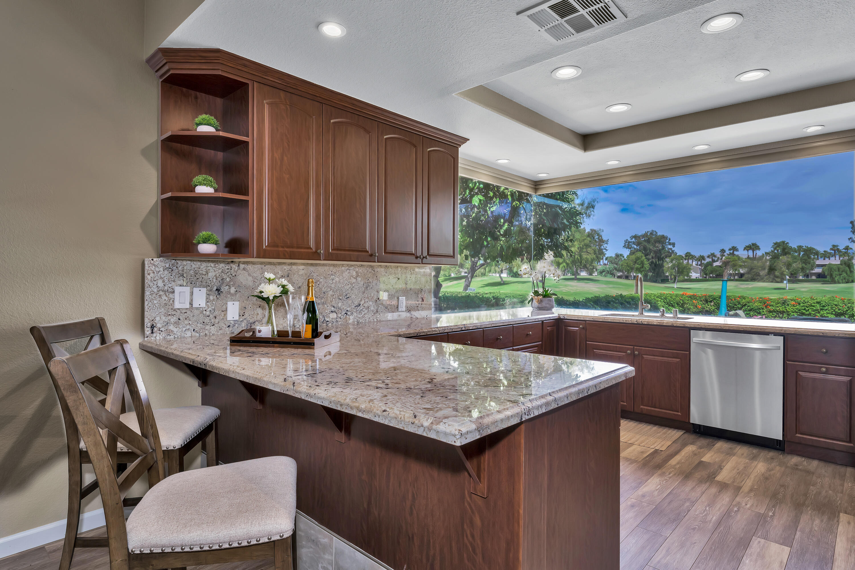 Enjoy Serene Golf Course Views from this designer renovated home in Mission Hills Country Club. This popular single level floor plan is on fee simple land (owned not leased) offering 1,806sf with 3 bedrooms and 2 bathrooms. The luxurious kitchen has granite counters with a matching full height backsplash, beautiful cabinets, new stainless-steel appliances, a breakfast bar and stunning views through the oversized frameless windows. The Great Room offers endless enjoyment with volume ceilings, wet bar, stunning tile fireplace and direct access to the back entertainment patio. Both bathrooms have been completely transformed with modern tile work in the showers, quartz vanity tops and the dual sink master bathroom has an impressive tiled soaking tub. Modern Window Coverings and plantation shutters, gorgeous tile work in showers, lighting fixtures, ceiling fans and upgraded flooring are just some of the new features the current owner has added to this move-in ready home. The rear patio maximizes great views and is sure to provide many enjoyable desert days and nights. There is also a 2-car + golf cart garage convenient for enjoying the country club or adjacent Westin Resort. This is the perfect package to start enjoying the country club lifestyle.