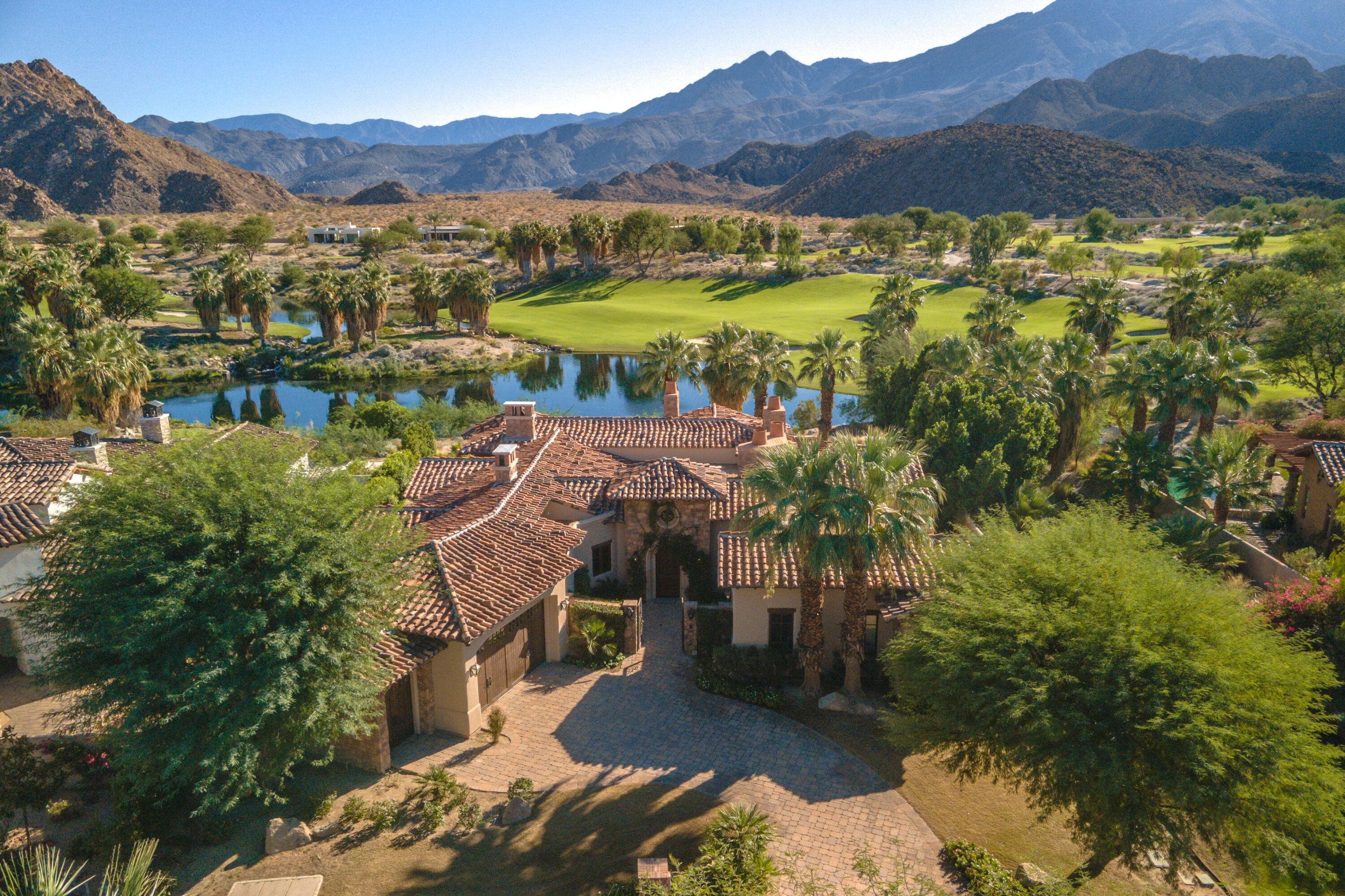Incredible Estate Behind The Gates Of The Quarry.  With 4,161 sq ft of interior living space, this exquisite 4 bedroom & 5 bathroom home is located on a lake with stream & the lush green golf course.  The south facing backyard has an oversized pool & spa, wrap around patio & outdoor kitchen with sweeping panoramic views of Coral & Santa Rosa Mountains.  Upon formal entry, feel the richness of stone walls & wood floors.  Recently remodeled kitchen features white cabinets, quartz counters, Subzero refrigerator, Viking Stove & opens to the living room.  Living area features wood beam ceilings, fireplace & walls of glass opening to the course & mountains.  Separate oversized den with fireplace is currently a game room & could also be a media room.  Elegant master suite with fireplace has dual walk in closets, separate tub & walk in shower plus dual vanities.  Two additional en suite bedrooms in main residence.  Casita with wood beam ceilings opens to the courtyard.  The Old World charm & contemporary touches make this an incredible home with one of the best views in The Quarry.  Home is strategically located very close to the clubhouse.  The Quarry is a highly rated private golf community with an 18 hole executive & top tier short course.  Home is being offered turn key furnished.