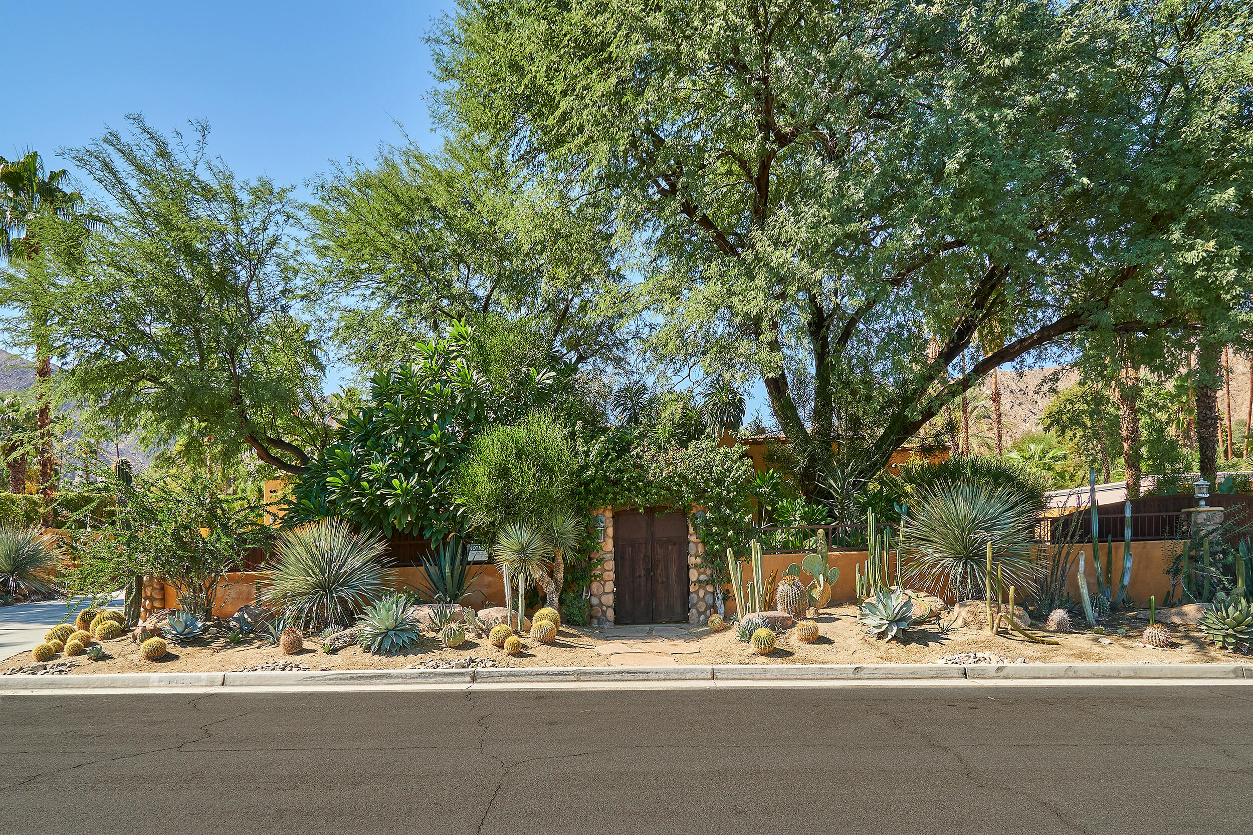 RARELY AVAILABLE:  Quality, CHARMING Spanish in Magnesia Falls Cove! Large lot, south- facing back yard with mountain views. Completely walled and double gated with wood and steel. Amazing finishes and authentic touches throughout. 4 Beds and 5 baths in total. Separate casita PLUS a huge garage PLUS bonus room and bath.  Entertain in this spectacular resort setting with unique pool and spa in a garden paradise of citrus trees, palms, plumeria and specimen cactus. Open & well appointed kitchen sets the tone for gracious living and relaxing dinners. Fountains, water features, palapas and outdoor showers might inspire you to make this unusual offering your new, luxurious desert retreat.