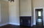 Living room with hardwood floors and beautiful firplace with great detail.