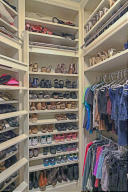 HER MASTER CLOSET WITH CUSTOM BUILT-INS