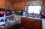 Terrazzo floors. Laminate countertop. Window looks out to back of house. Lots of cabinets