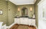 Oversized Powder Room just off the Foyer features Furniture Vanity with Glacier Finish and French wall sconces.