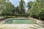 In-ground gunite swimming pool has stamped concrete surround