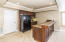 Wet bar area in basement has tile floor wood cabinets, sink with disposal and refrigerator that conveys with home
