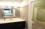Tiled master bath with refurbished solid surface vanity and elegant updated lighting & mirror! Separate commode & shower area with tile floors and brushed nickel glass shower door!