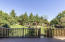 Private fenced back yard with tons of professional landscaping and a pond with water feature