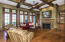 Elegant arches lead you to the Gallery and open to a spacious Family Room. Warm stained trim includes hand crafted Box Beam Ceiling, Custom Mantle and Built-ins.