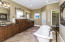 The elegant bath suite has a sumptuous double slipper French bathing tub, and a walk-in tiled shower with exciting features such as multiple body sprayers, wall shower head, opposing wall hand-held sprayer and an oversized rain showerhead. Separate his and her walk-in closets and rich custom cabinetry and granite tops add the final touch to this important space.