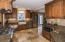 The spacious kitchen has travertine floor, wood cabinets & granite counter tops
