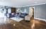 Large living room has hardwood floor, crown molding & built-in shelving