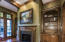 Full Masonry Fireplace with custom mantle is flanked by pair of arch top built-ins