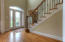 Inviting vaulted foyer with oak solid stairs and iron rails.