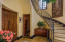 The entrance hall with graceful stone stairwell and guest powder room.