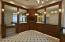 master bath with large mirrors, cherry cabinets, solid surface counters