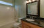 Main-Level Bathroom - convenient for guests, it's updated with gorgeous granite-topped cabinet, updated lighting & mirror