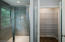 Glass enclosed tiled shower, linen closet in master en suite