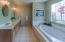 Master Bathroom with double vanities, shower, jacuzzi tub, and walk-in closet