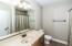 Full Bathroom in basement has wood cabinet & tile floor