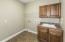 Laundry Room is located near Master Bedroom & has wood cabinets & tile floor