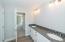 Dual vanities, granite countertop, tile flooring, and large linen closet
