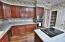 Kitchen has stainless appliances, hardwood floors.