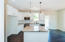 White Shaker style cabinetry with crown molding, granite countertops, white subway tile backsplash