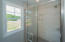 Ceiling to floor tiled shower with shampoo nook, and glass enclosure