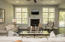 Gas fireplace centers the living room with large windows on either side